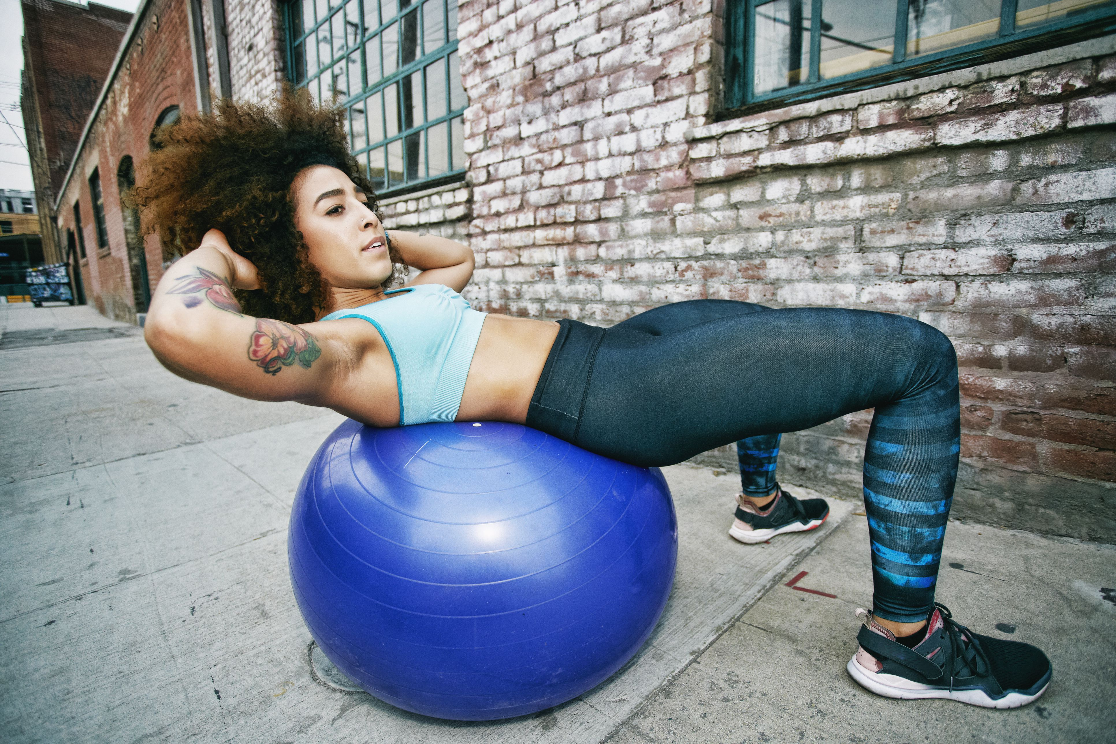 Mujer hispana de equilibrio sobre la pelota de fitness cerca de la pared de ladrillo