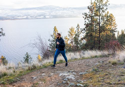 hombre caminando rápido por sendero de montaña costera