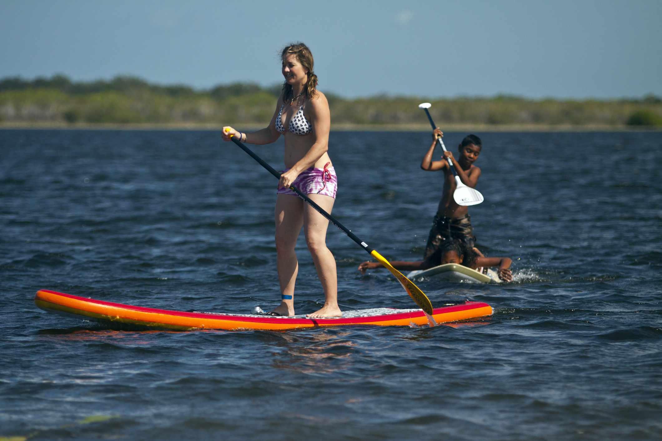 Adolescente y niño paddleboarding en un lago