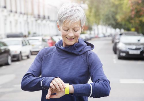 Mature woman checking activity tracker outside