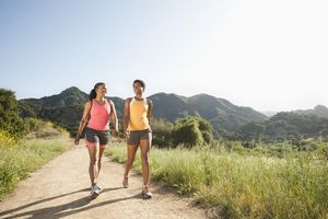 Two athletic people walking outside together on a trail