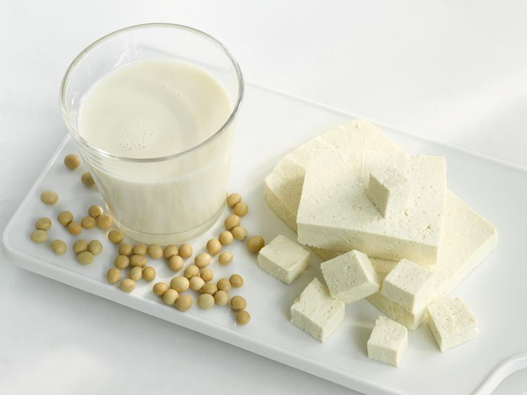 Tofu, soya milk and soya beans in tray, close-up