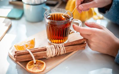 Woman stirring teabag in a cup of cinnamon tea surrounded by a cinnamon stick and lemon