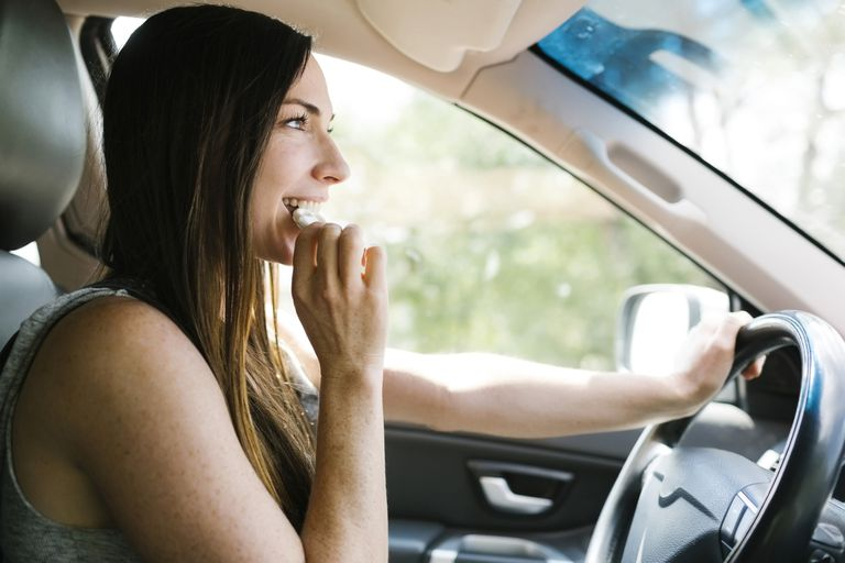 Smiling woman driving car and eating pretzel