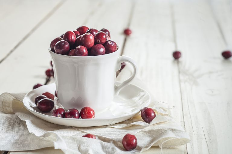 Fresh cranberries in a coffee cup - cranberries may help prevent bladder infections.