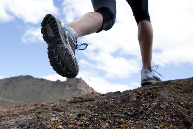 Female's legs trail running on rocks.