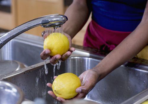 una mujer lavando limones en un fregadero