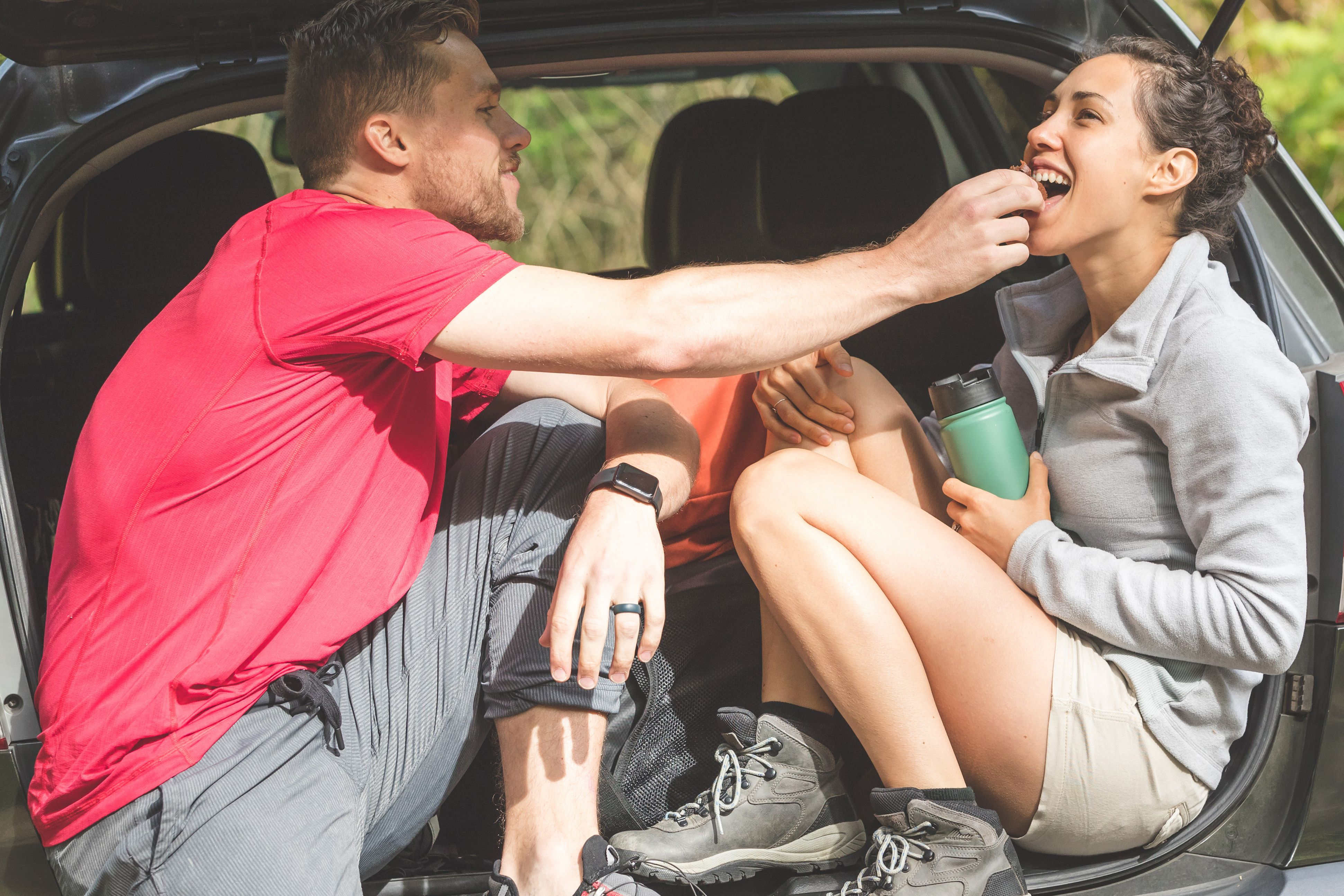A young couple eats snacks in the back of their car after hiking
