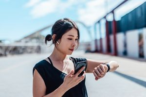Young women wearing earbuds and holding phone