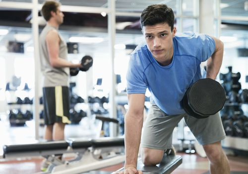 Young man lifting dumbbell in the gym