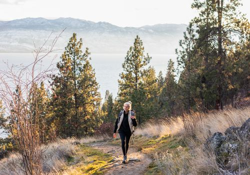 senior woman walking in woods on a coastal mountain trail