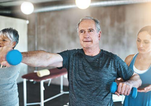 Hombre usando pesas en una clase de fitness