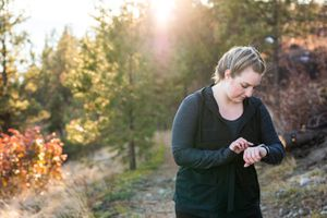 woman walking for fitness in the woods and checking tracker on watch