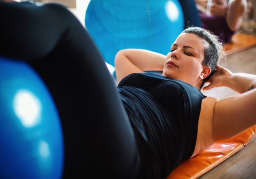 Woman doing abs exercise on fitness ball