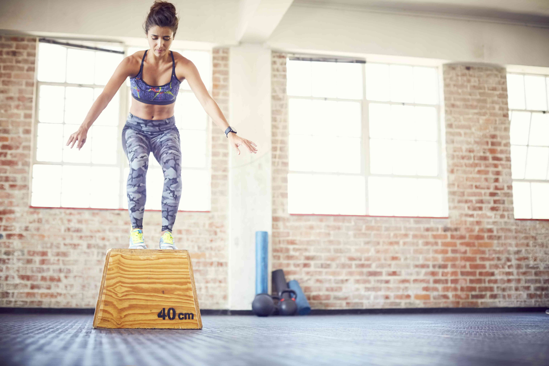 Atleta femenina ejercicio de salto de caja en el gimnasio