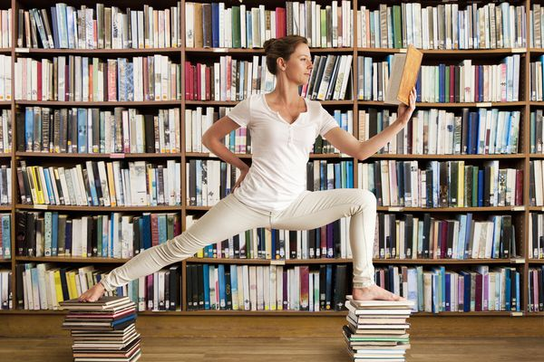 Woman in library reads book and holds yoga pose