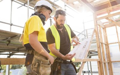 Contractors looking at plans on a building site