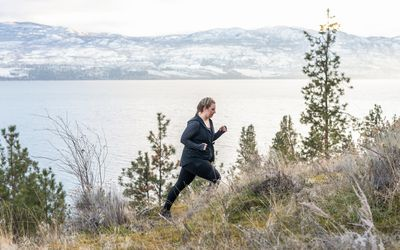 woman walking for fitness uphill on a mountain trail along the coast