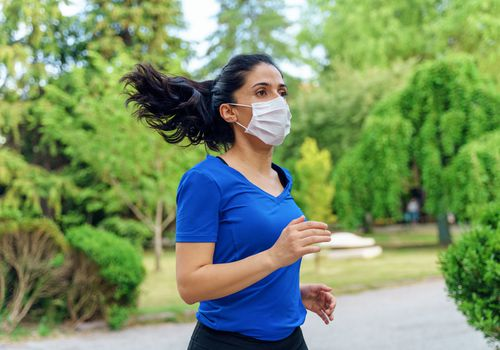 Woman wearing surgical mask running outdoors