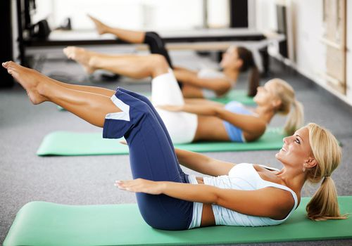 Three women doing Pilates mat exercises