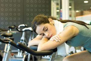 Woman asleep on an exercise bike