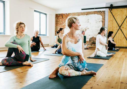 Un grupo de amigos practicando yoga juntos en un estudio moderno.