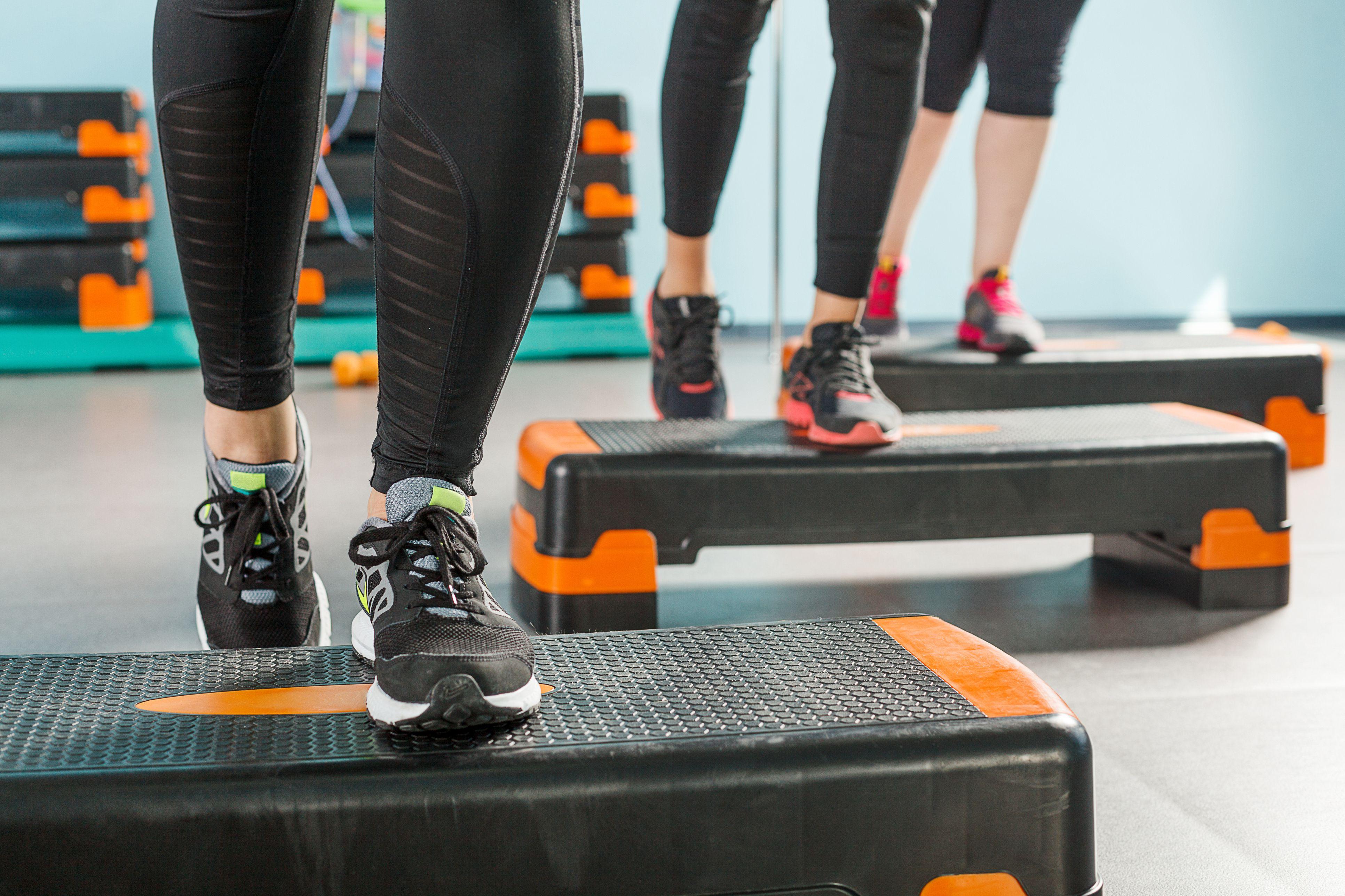 primer plano de las piernas de tres mujeres subiendo a un escalón de ejercicio