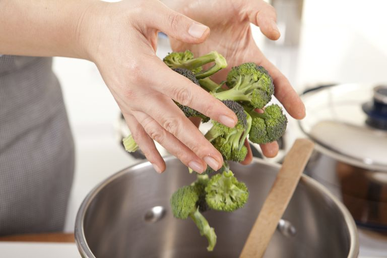 woman's hands tossing broccoli into pan