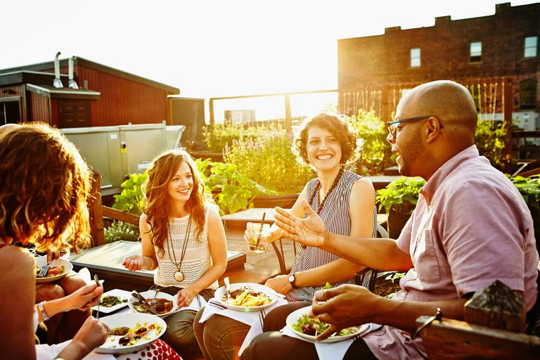 Laughing group of friends dining in rooftop garden