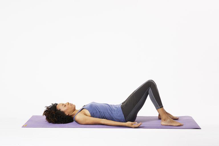 Woman lying on yoga mat doing three-part breath