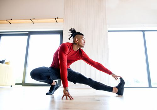 A portrait of fit man doing exercise at home, stretching.