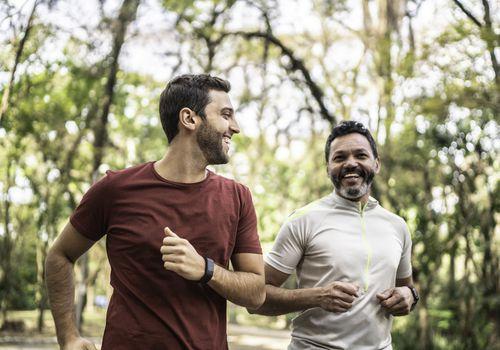 Amigos varones corriendo juntos en un parque