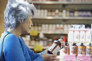 Senior Asian woman reading vitamin label