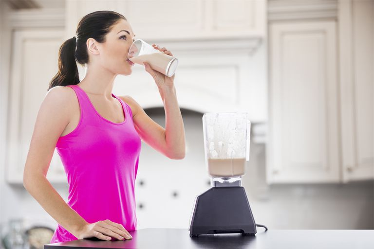 Caucasian woman drinking smoothie in kitchen