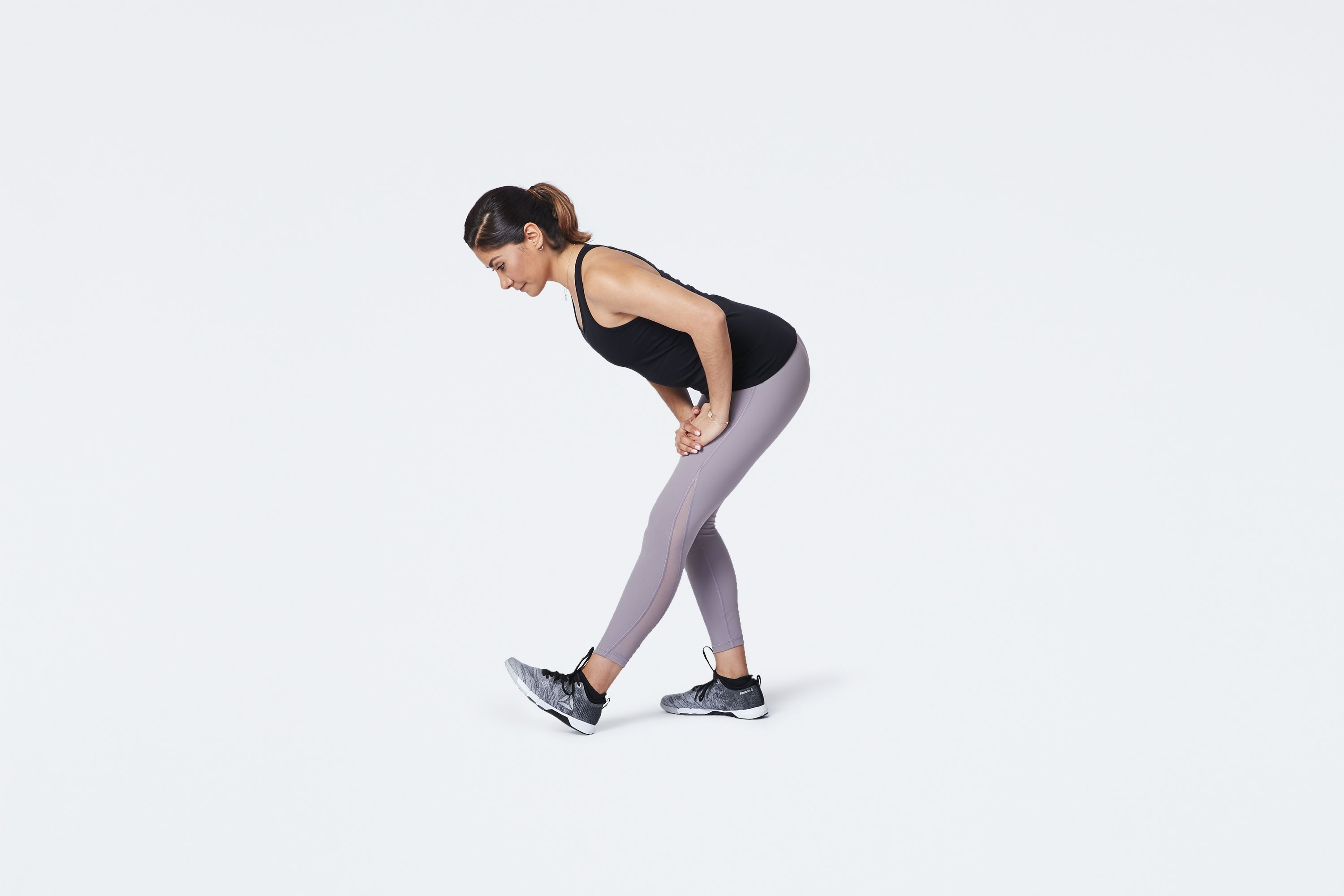 woman stretching hamstrings while standing