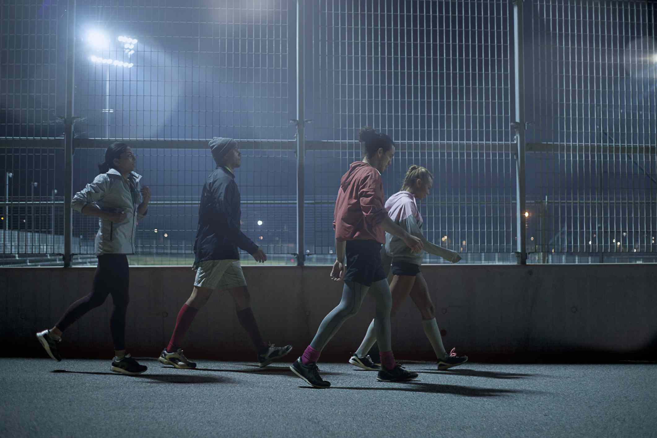 two men and two women walking at night around a track