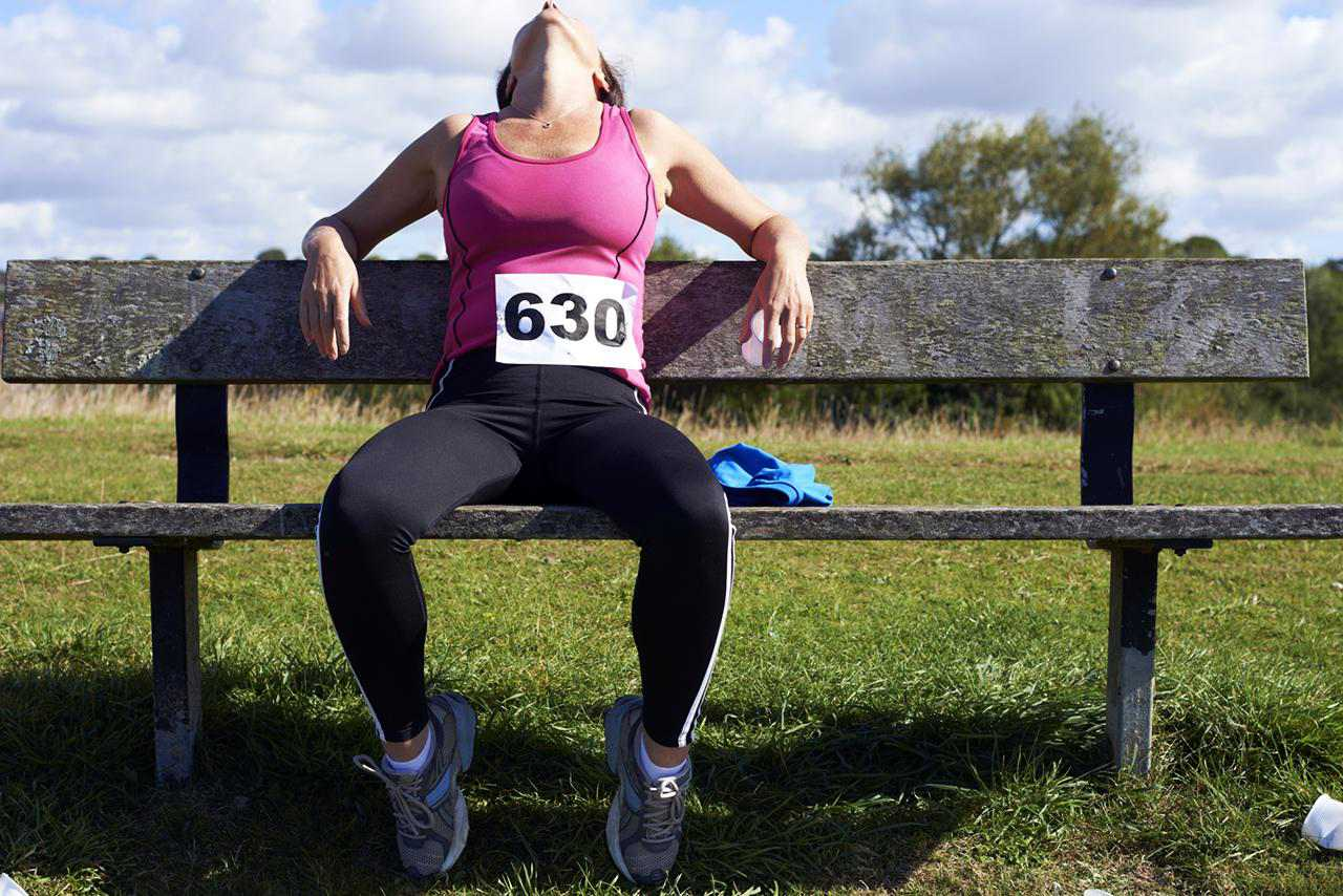 Runner resting on a bench after a race