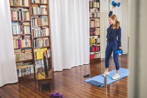 a woman lifting weights at home