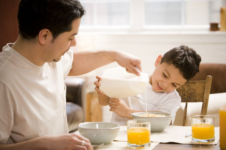Father and young son having breakfast together