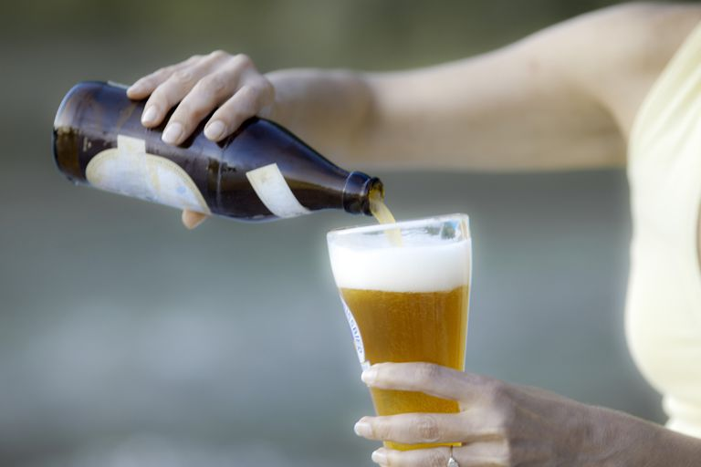 woman pouring beer into glass