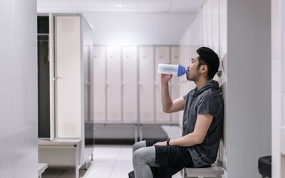Tired man drinking protein shake after workout