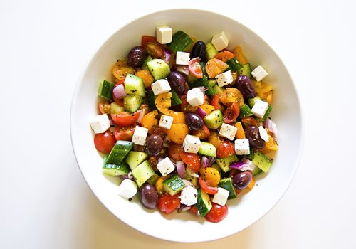 Close-up, high-key image of a white bowl filled with a Greek salad, including tomatoes, cucumber, olives, onions and feta beans - stock photo