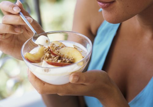 Woman eating yogurt topped with peaches