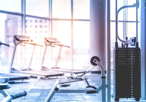 Torre de pesas y cintas de correr en un gimnasio vacío