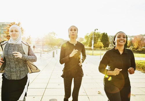 Three women exercising outside.