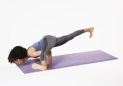 Woman on yoga mat in hurdler pose