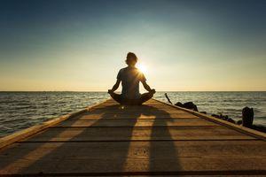 man meditating on pier