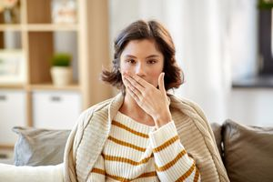 woman holding hand over mouth bad breath
