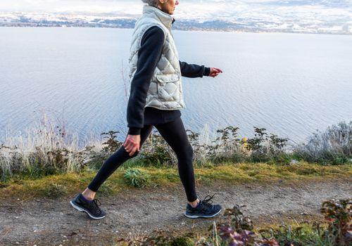 senior woman walking on coastal mountain trail