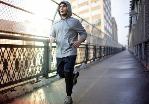 Hombre adulto corriendo por un puente